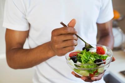 closeup man holding salad