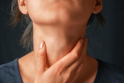 closeup of woman touching throat