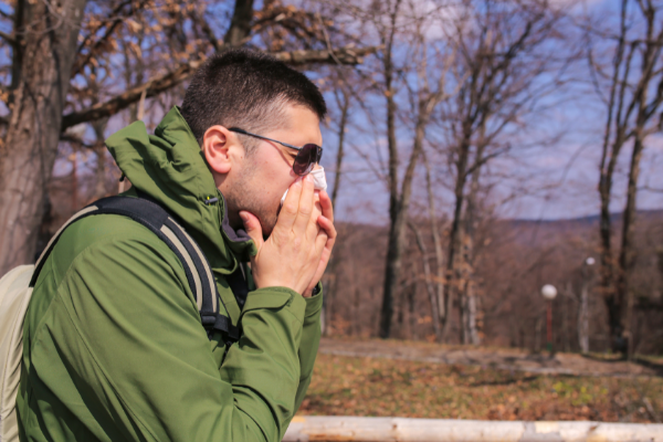 man blowing nose outside