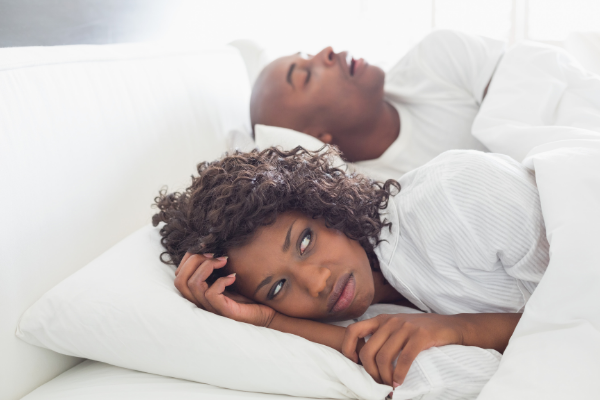 wife annoyed by husbands snoring in bed