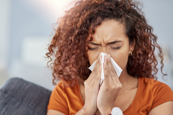 woman blowing nose with tissue