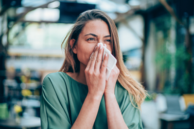 woman outdoors wiping nose